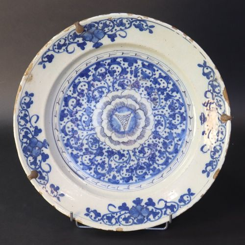 DELFT XVIIe  Plat circulaire en faïence à décor bleu blanc d'une fleur au centre…