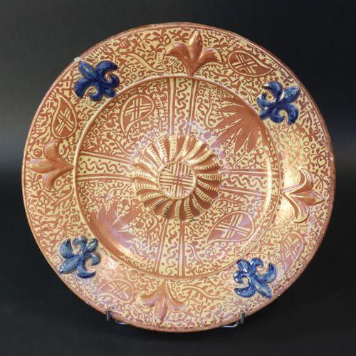 HISPANO MAURESQUE  Plat en céramique à décor lustré et fleurs de lys.  Diam. 36.…