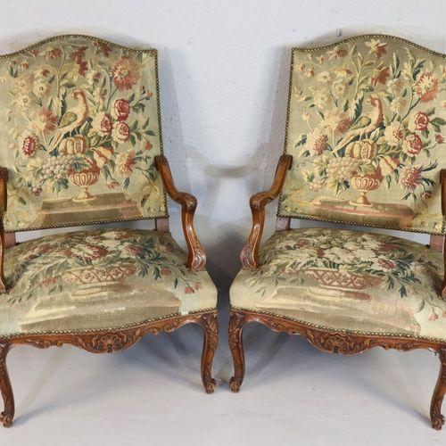 Paire de fauteuils en bois naturel à dossier plat, le fût à décor sculpté de coq…