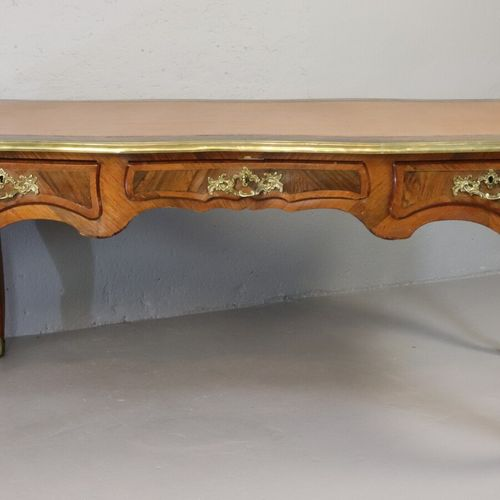 Bureau plat en placage de palissandre ouvrant par trois tiroirs en ceinture, orn…