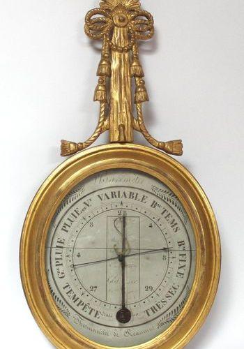 BAROMETRE de type Réaumur en bois doré, le corps ovale, le support orné d'un nœu…