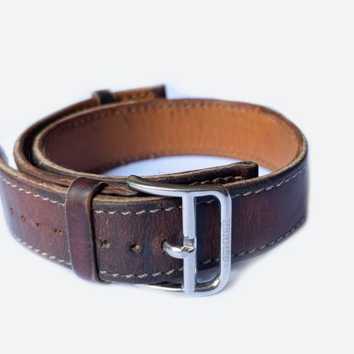 HERMES. Bracelet de montre en cuir marron à surpiqures blanches, double tour. Bo…