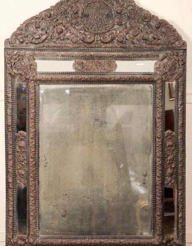 Important MIROIR A PARECLOSES en bois noirci à riche décor en métal repoussé de …