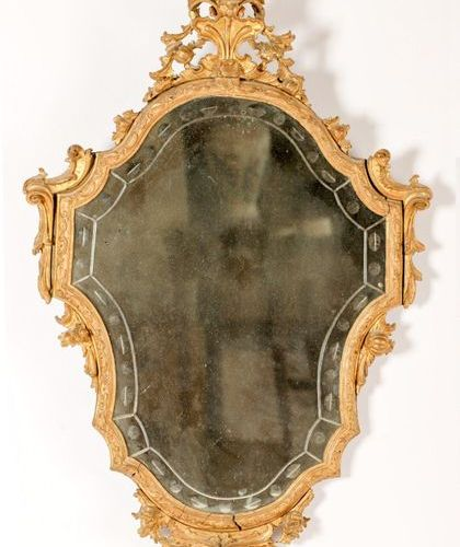 MIROIR de forme chantournée en bois sculpté et doré à décor rocaille, surmonté d…