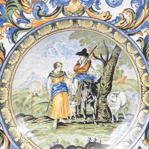 PLAT CREUX circulaire en faïence à décor polychrome d'une scène pastorale. Le ma…