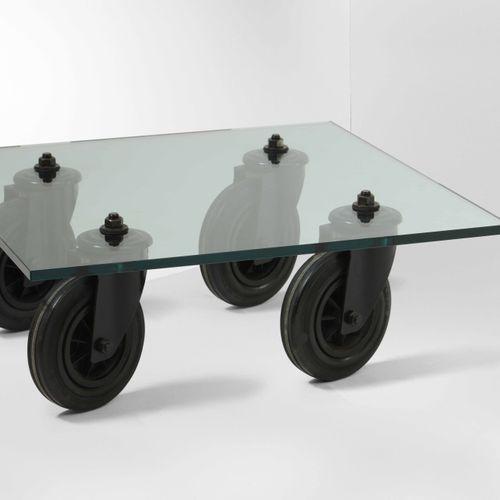 Gae Aulenti, Table basse avec plateau en verre dépoli. Supports de roues en méta…