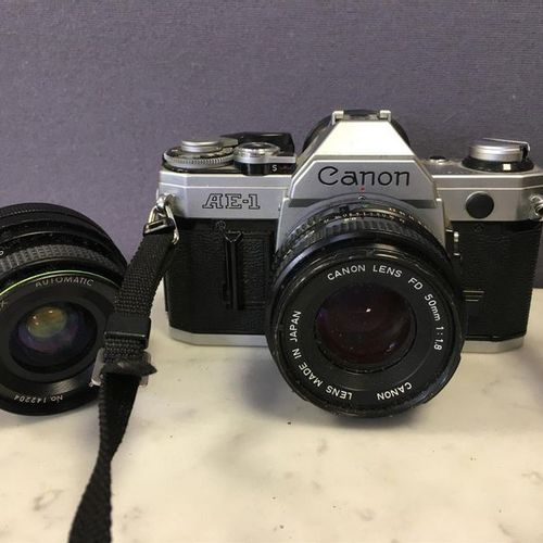 CANON AE 1 camera, with its 1:1.8/50 mm lens. A 1:2.8/49 mm HANIMEX lens is incl…