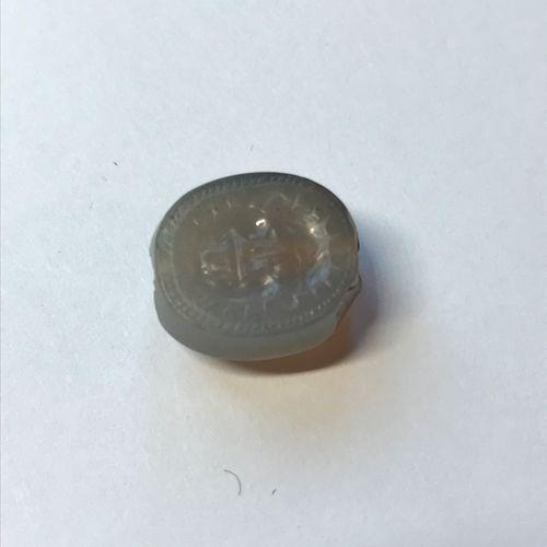 Scaraboïde en calcédoine bleutée, le plat gravée d'une tête de gorgone grimassan…