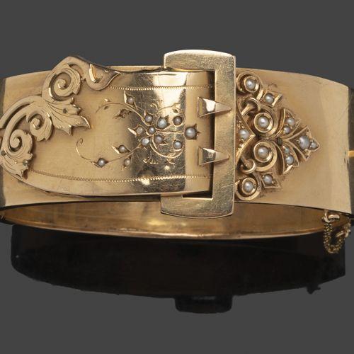 Bracelet rigide en or jaune formant une boucle ornée de motifs feuillagés sertis…