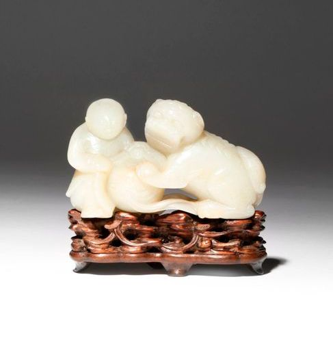 A CHINESE PALE CELADON JADE CARVING OF A BOY AND A LION DOG QIANLONG 1736 95 The…