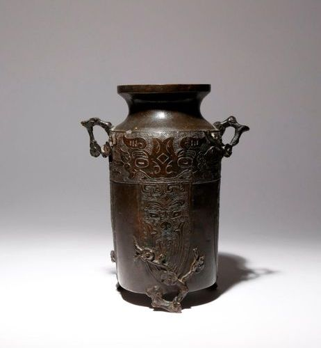 A CHINESE ARCHAISTIC BRONZE VASE MING DYNASTY The tall cylindrical body surmount…