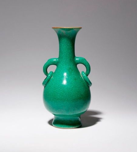 A CHINESE GREEN GLAZED PEAR SHAPED VASE LATE QING DYNASTY Rising from a spread f…