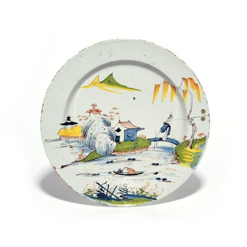 A delftware plate or charger c.1750 60, decorated in polychrome enamels with a f…