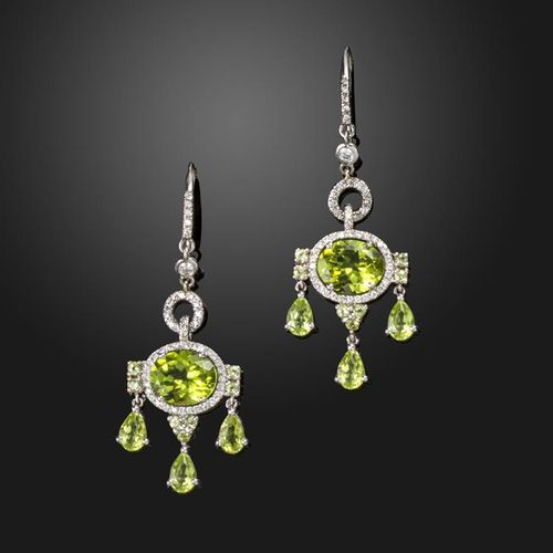 A pair of peridot and diamond drop earrings, each set with an oval shaped perido…