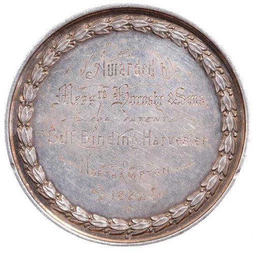 北安普敦郡农业协会:一枚重银奖牌。51毫米,一蒲式耳小麦,前景为犁和农具,背面刻有(授予Messrs Hornsby & Sons专利自缚式收割机Northam…
