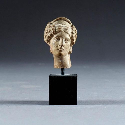 Petite Tête féminine. With curly hair and a tiara. Terracotta. About 4th century…