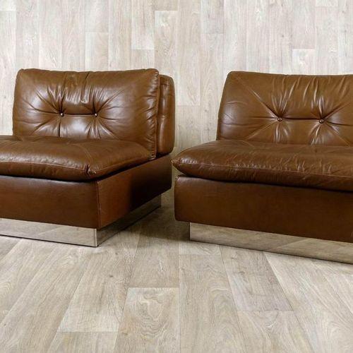 Suite de deux Fauteuils Lounge. Entièrement garnis de cuir brun. Base en alumini…
