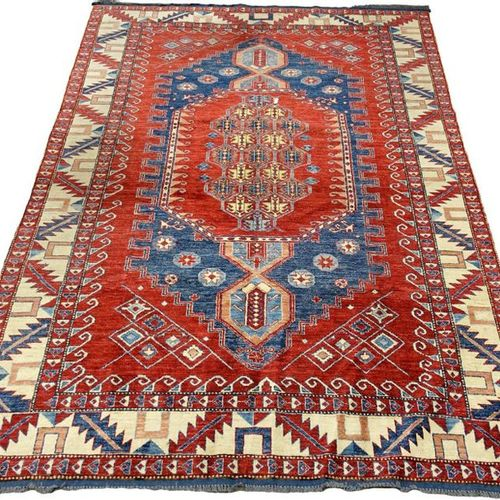 Tapis Kazak. Large medallion with red background and blue background. Framed wit…