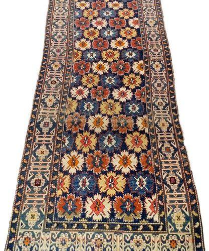 Tapis Caucase. Le fond est décoré, en plein, de fleurons polychromes. Bordure gé…