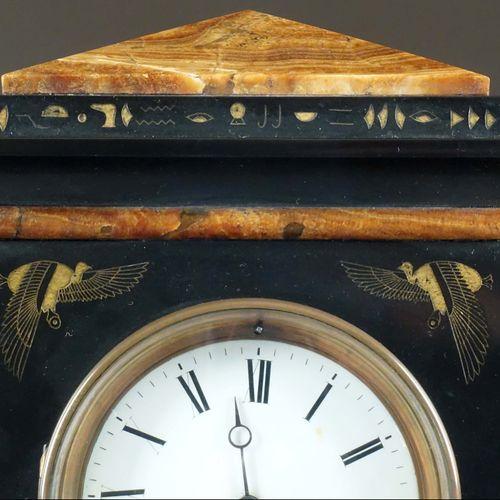 Garniture de Cheminée à l'égyptienne. Formée d'une pendule prenant la forme d'un…