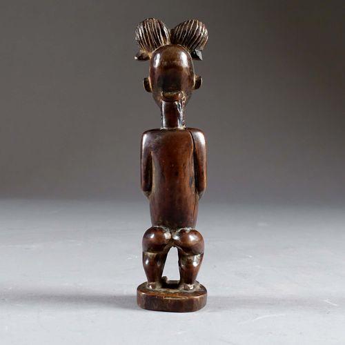 Statuette Baoulé. Figurant un personnage debout, les mains posées sur l'abdomen …