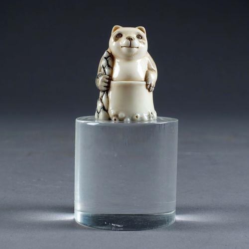 Rare Netsuké. Figurant un panda assis dans un bassin. La base gravée d'une branc…