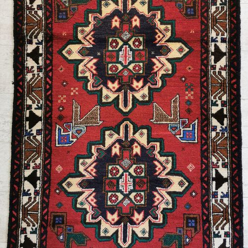 伊朗。羊毛巴鲁什地毯,在红底上装饰着两个蓝色的奖章,上面有几何图案和风格化的花朵。86 x 133厘米。