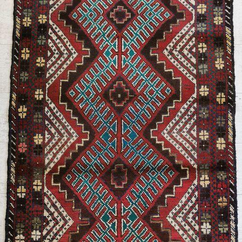 伊朗。羊毛巴鲁什地毯,中央饰有红底三个交错的绿色菱形图案,边框饰有风格化的花朵。84 x 138厘米。