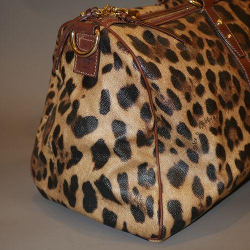 DOLCE GABBANA. Sac de voyage en cuir à motif léopard. Fermeture zip. Doubles ans…