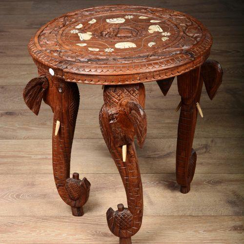 Table basse à quatre pieds en protomé d'éléphant. Tablette circulaire scuptée de…