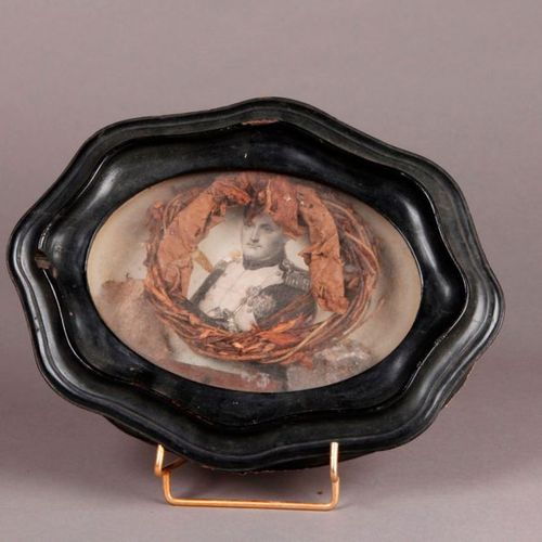 HISTORICAL MEMORY. An oval frame of moving form made of blackened wood with an e…