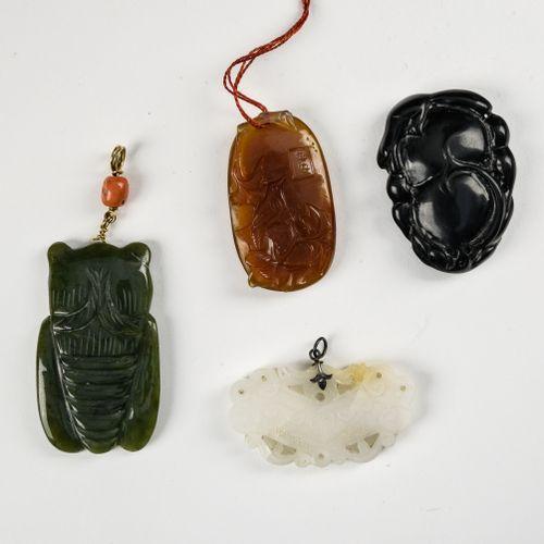 Quatre pendentifs  CHINE DÉBUT XXE SIÈCLE  L'un en agate brune à décor d'oiseau …