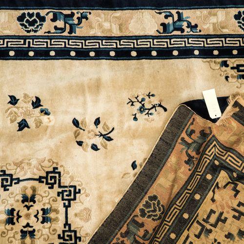 Tapis CHINE  Tapis    Fond crème, décor bleu et tabac d'un médaillon fleuri dans…