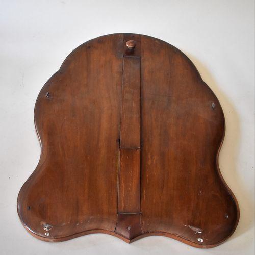 GLACE DE TABLE mouvementée en bois de placage à frise de perles en laiton. Au ve…