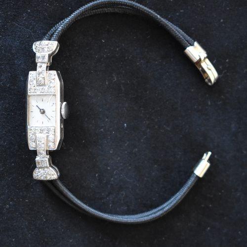 MONTRE DE FEMME en platine à pavage de roses, bracelet double cordon. Poids brut…