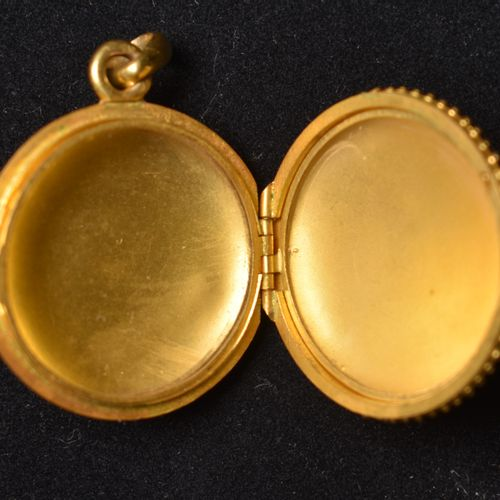 MÉDAILLON RELIQUAIRE en or jaune 18K (750) orné d'émail, figurant un amour tenan…