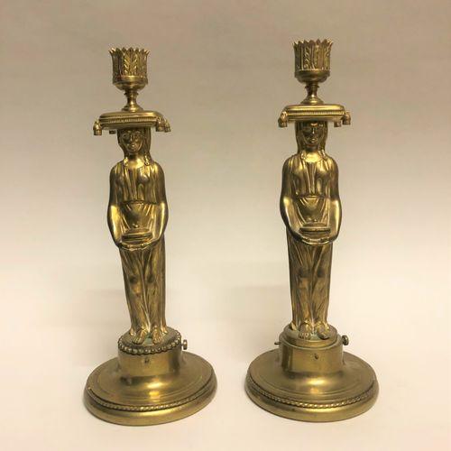 Paire de FLAMBEAUX en bronze ciselé et doré à décor de cariatides tenant dans le…