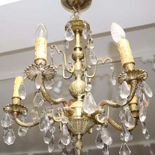 A chandelier with bronze pendants and arms of lights