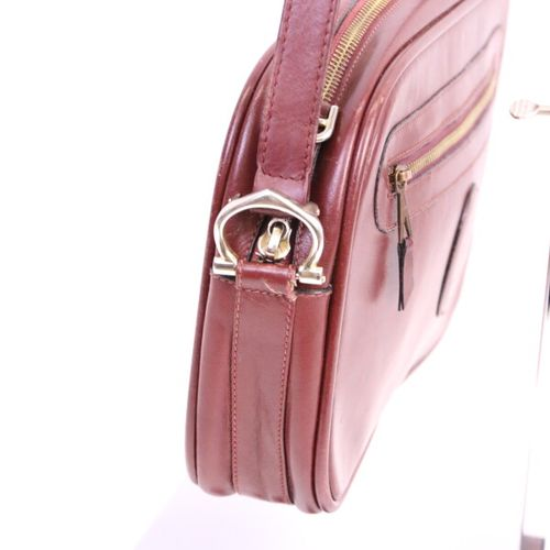 CARTIER  Burgundy leather messenger bag, closing with a zip, burgundy canvas int…