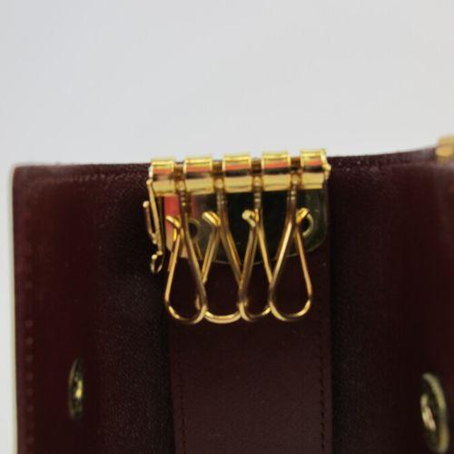 CARTIER Must de Cartier  Key case in burgundy calf leather, monogrammed embossed…
