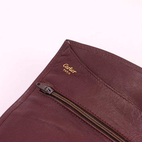 CARTIER  Burgundy leather jewellery pouch, inside a large pocket, two zipped poc…