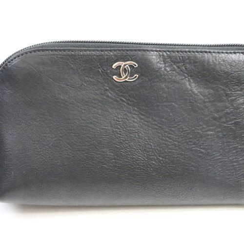 CHANEL  Pochette en cuir noir zippé, siglée.  21 x 12 cm