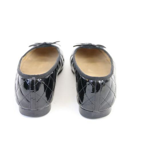 CHANEL  Paire de ballerines en cuir vernis noir matelassé, siglées sur le bout. …