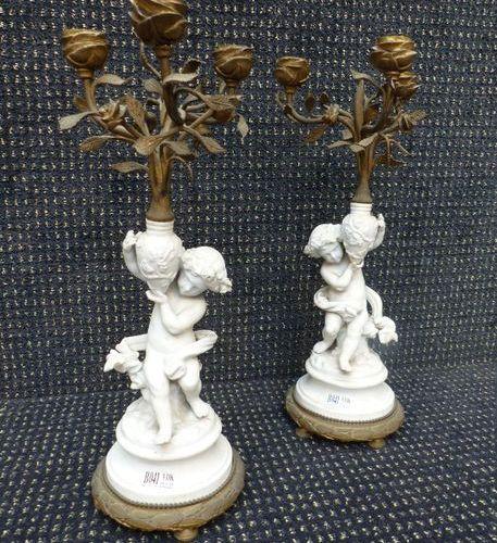 Une paire de chandeliers en biscuit et bronze XIXème siècle.