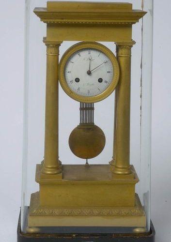 Pendule portique de style Restauration en bronze doré. Cadran signé F. Demanet à…