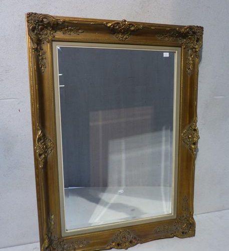 Un grand miroir rectangulaire en stuc doré.