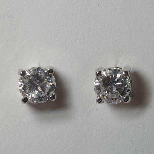 一对18K白金耳环,镶嵌两颗明亮式切割钻石,总重+/ 0.71克拉(颜色:D E F;净度:VS SI)。总重量: +/ 1,1gr.