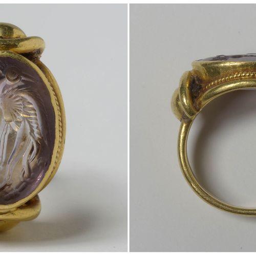 """戒指上镶嵌着紫水晶凹版,上面刻有 """"鹤和棕榈树 """"的印章。米诺斯时期,克里特岛。镶嵌方式为22K黄金。手指(公制):53 54。总重量:+/ 11.6gr。"""