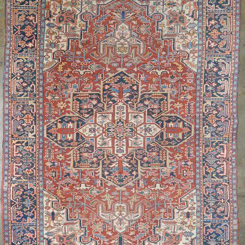 手工制作的大型羊毛Heriz地毯,在红白相间的背景上装饰着中央的蓝、白、红几何图章。波斯人的工作。尺寸:+/ 322x245厘米。