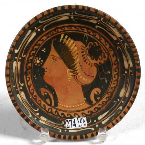 """黑色陶器小座盘,上面有红色的人物和白色的亮点,装饰有 """"女性头像的轮廓""""。由画家大流士和他的继任者 """"恩德沃尔德 """"的随行人员。作品来自意大利南部的阿普利亚。时…"""